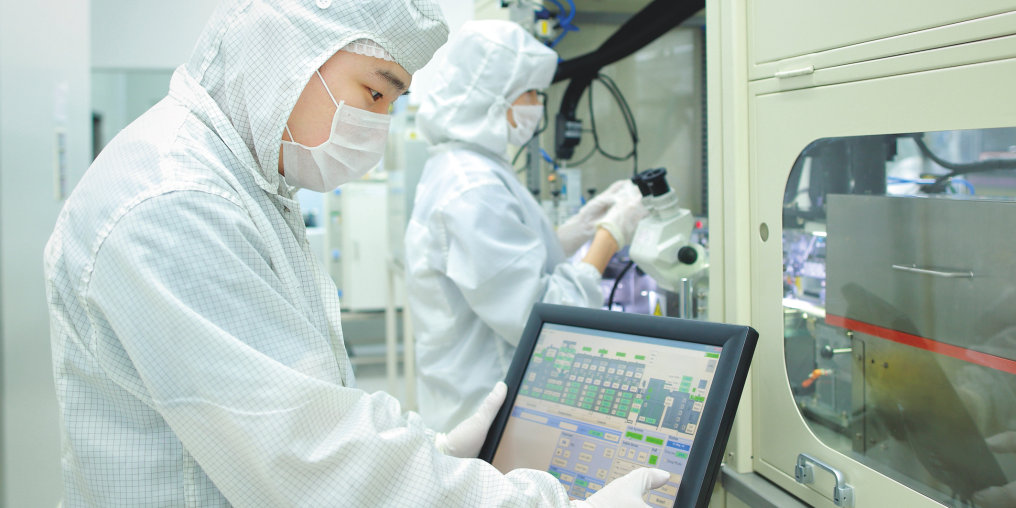 High tech in the OSRAM LED assembly in Wuxi: An engineer is standing in front of a machine for product testing.