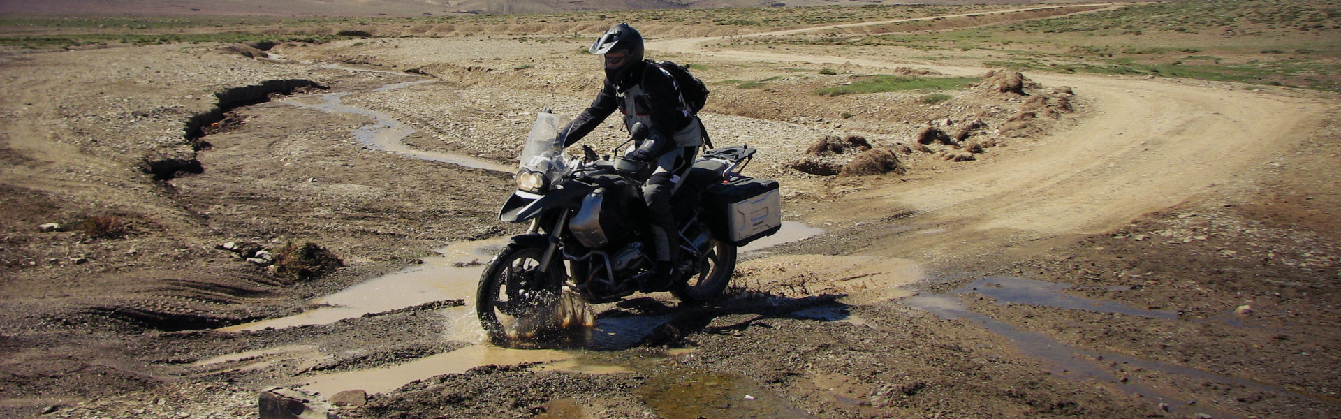 Motorcycle rider driving through mud