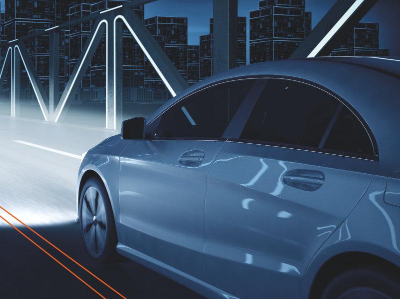 Bil med långa, ljusstarka strålkastarkäglor