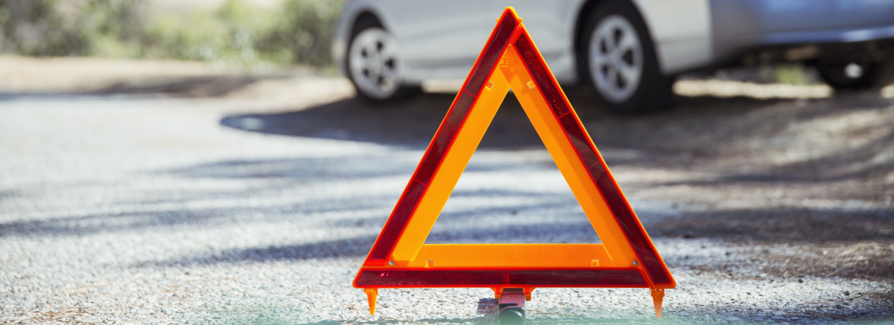 Warndreieck und Auto auf Seitenstreifen