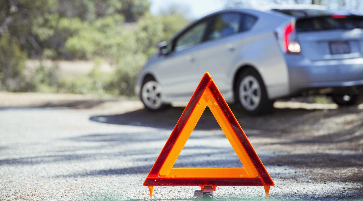 Triángulo de señalización y automóvil en el arcén